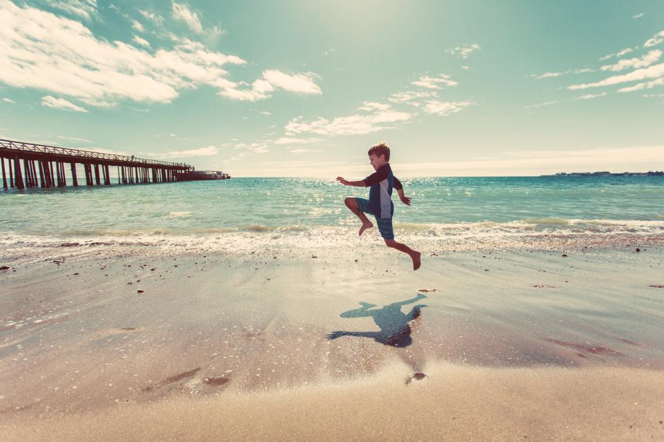 boy beach sand shore water waves ocean sea pier sunshine sunny summer sky clouds people fun jumping child