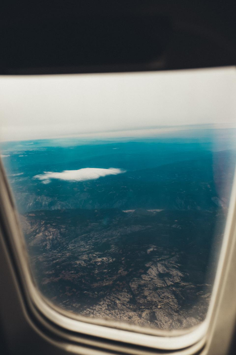 airplane window flying flight travel transportation trip aerial view mountains sky