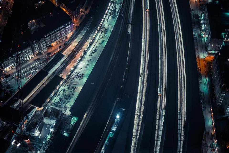 city urban train station dark night evening night lights cars roads driving buildings