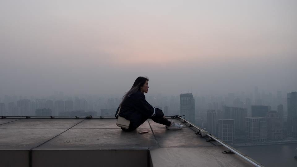 architecture buildings infrastructure rooftop fog cold people sitting girl alone thinking sad