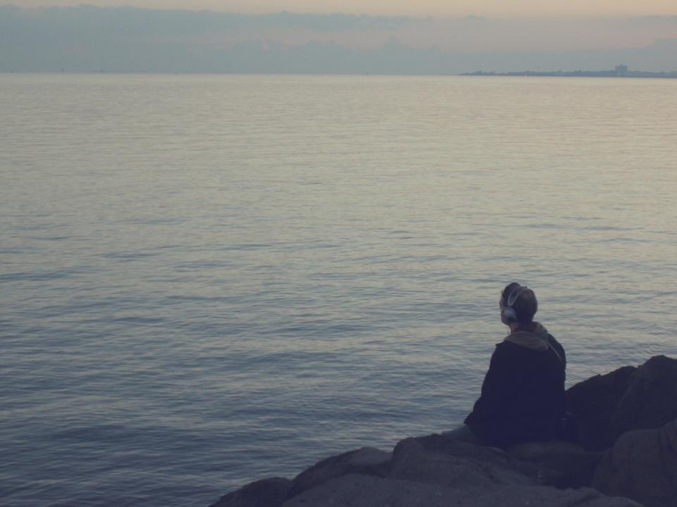 guy man headphones coast rocks water ocean sea lake water looking people