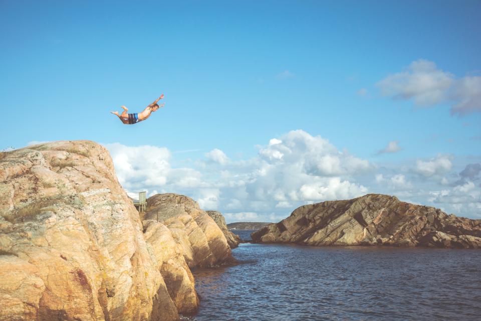 guy man diving swimming rocks cliff summer sunshine blue sky clouds outdoors adventure nature lake water ocean sea