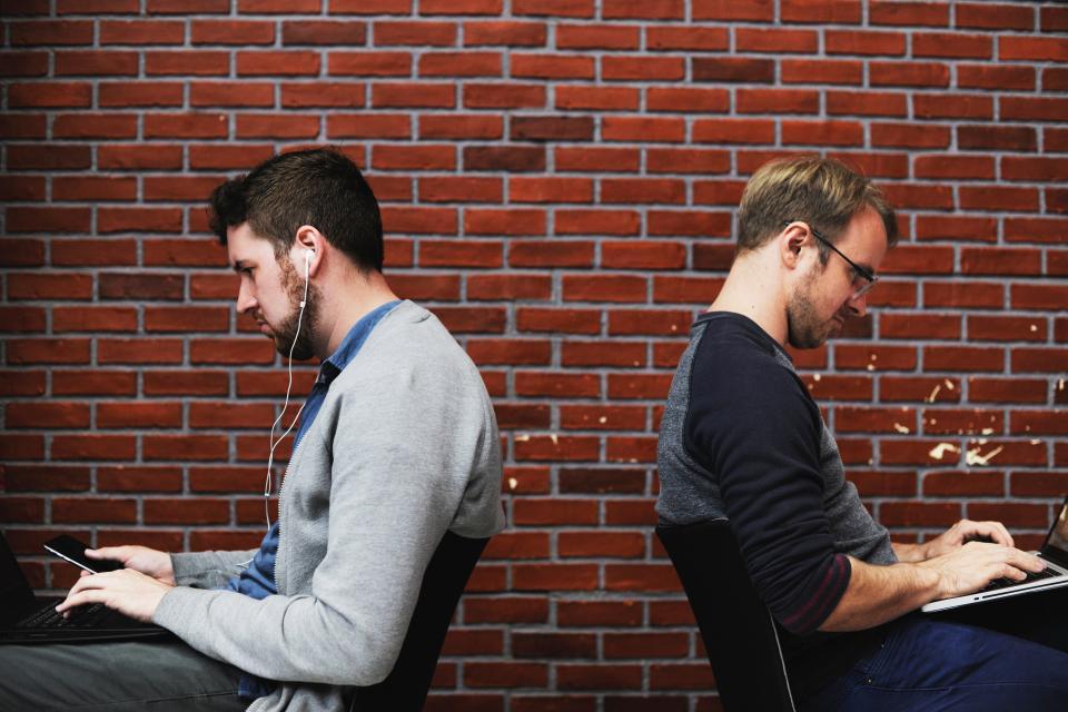 people men sitting chair browsing gadget laptop mobile phone electronic technology earphone music bricks wall brickwork workplace