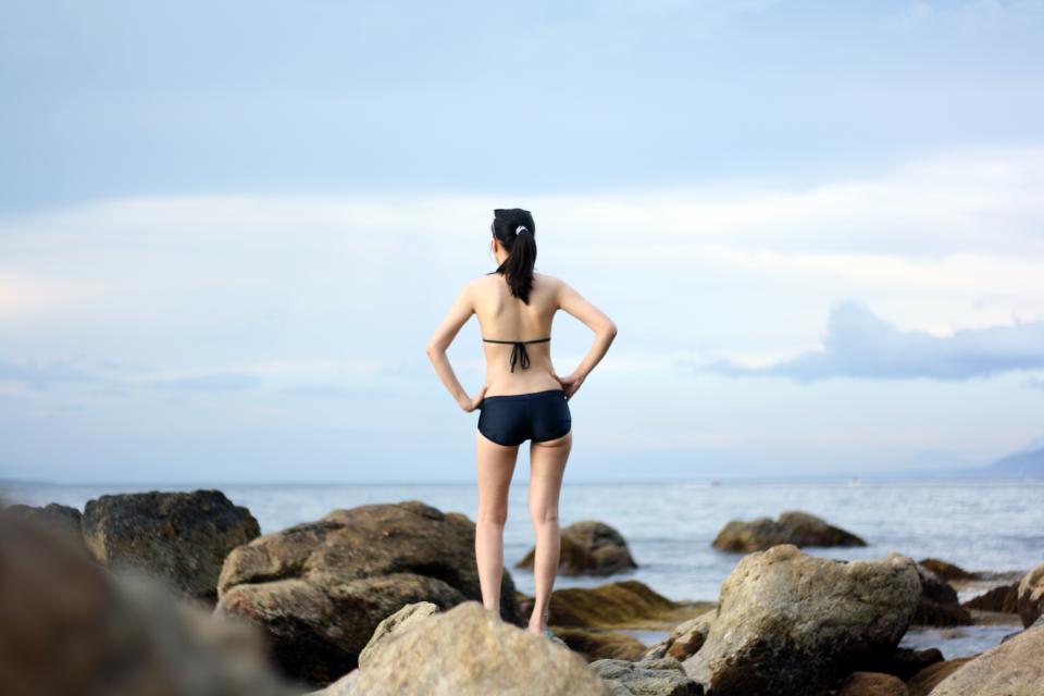 水着スタイルの岩海岸の水の海の海の空の雲の女性の女の子の女性は人バック