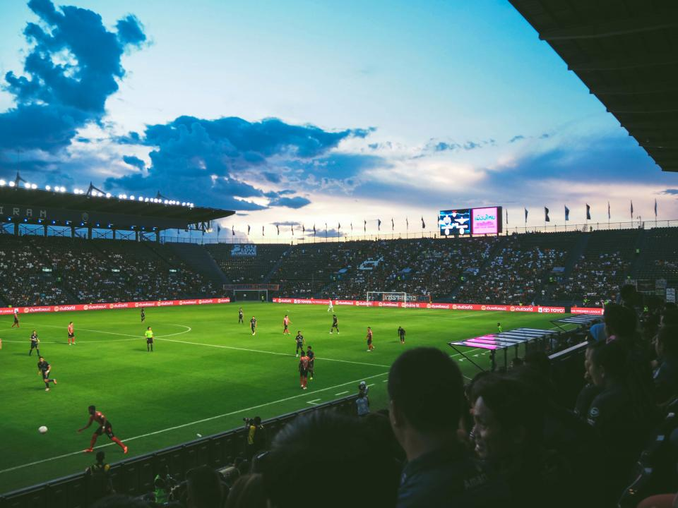 football, soccer, field, tournament, sport, game, people, crowd, men, women, players, competition, sky, clouds, dark, sunset, goal