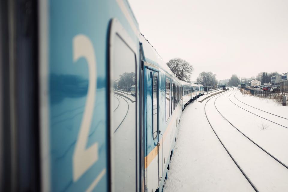 train, transportation, rail, track, trees, vehicle, houses, road, fog, sky, cars, park, fence, signage, posts