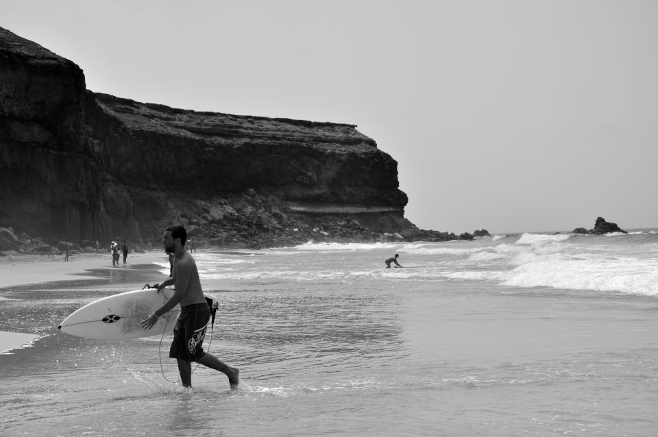 sea, ocean, water, beach, coast, shore, people, men, swimming, surfing, board, sport, black and white, hill, sky, waves, nature