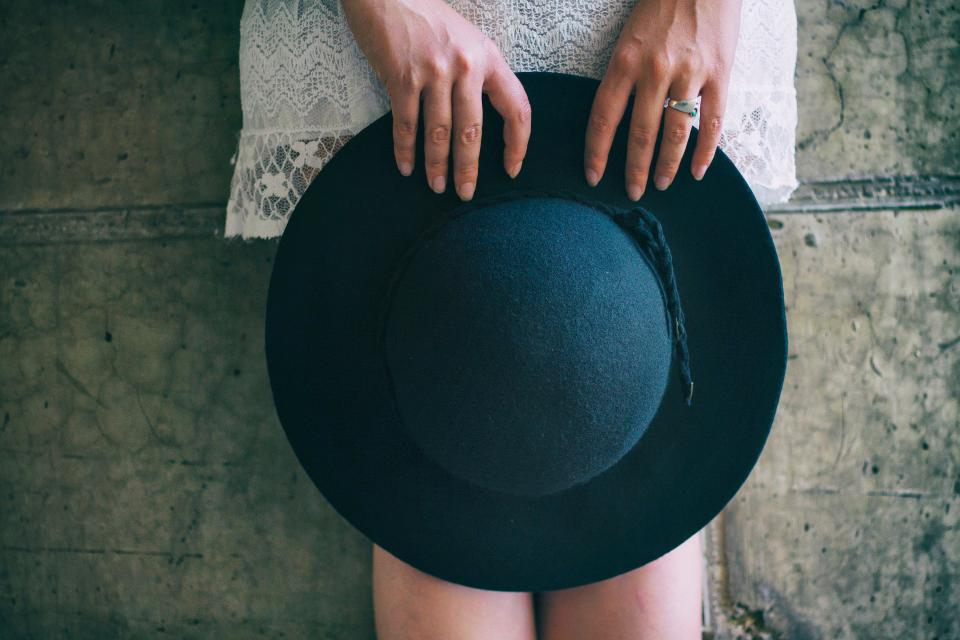 people girl woman female alone wall black hat hand ring