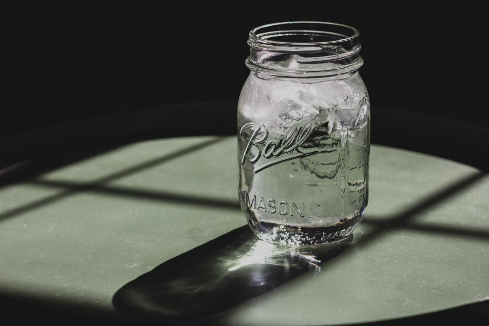 glass jar ice cold water table shadow dark room