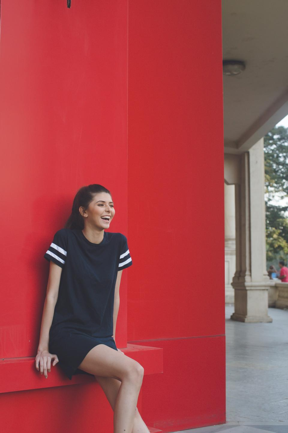 people, girl, woman, smile, happy, alone, red, wall, building, outside