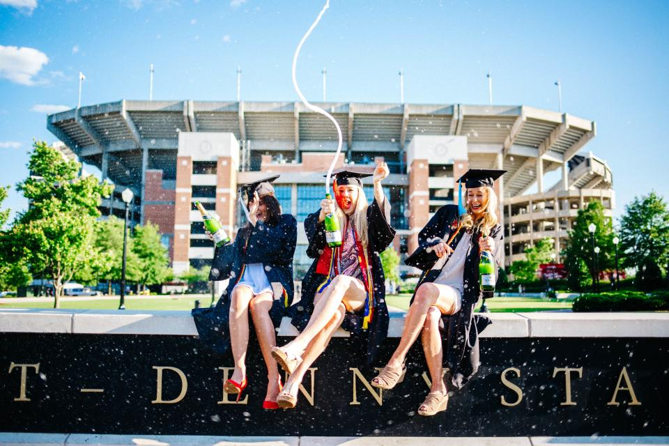people women girls student sitting graduate school building university graduation beverage champagne sparkling drink celebration blue sky field tree plant nature