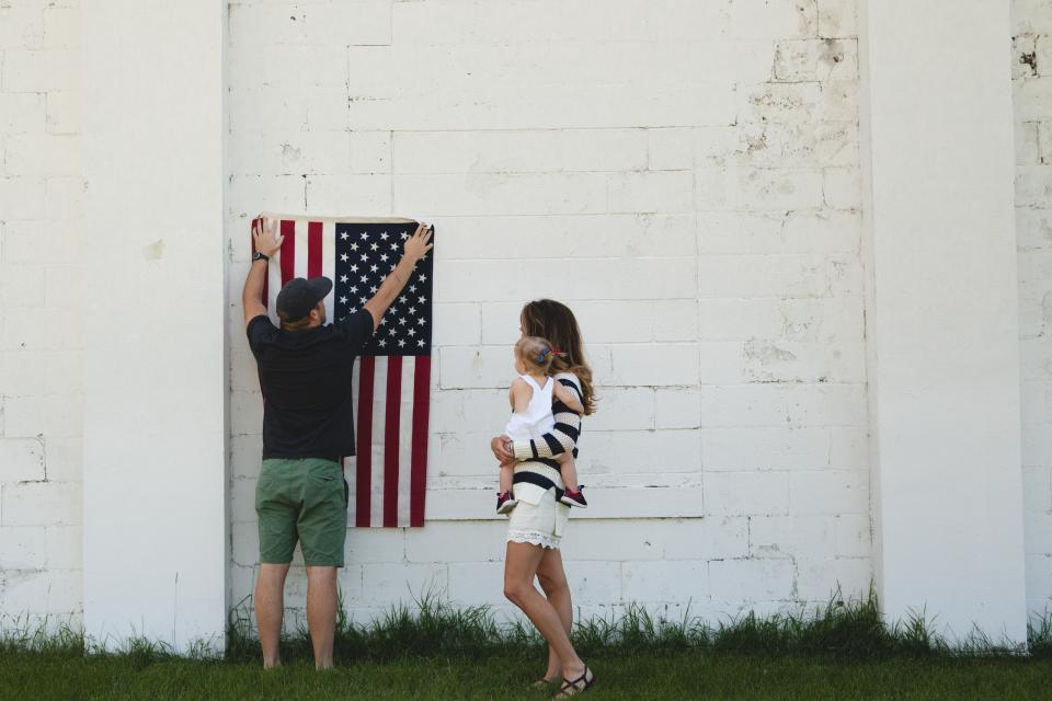 family, people, parent, mother, mom, baby, kid, child, cute, sweet, father, dad, flag, grass, wall, white