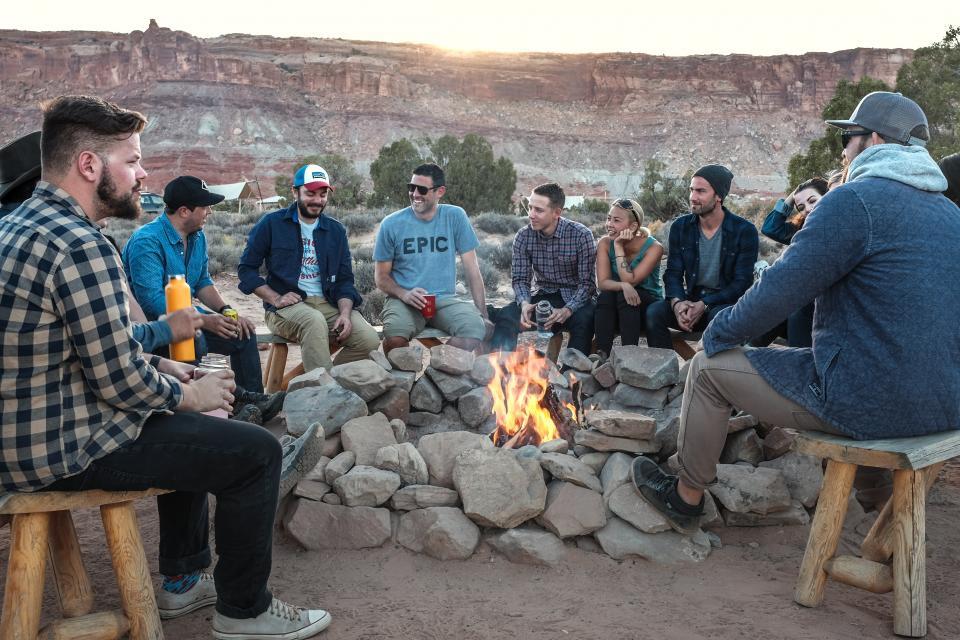 人の男性が炎キャンプ岩を発射木製のベンチの女性が幸せなグループの友人を笑う笑顔