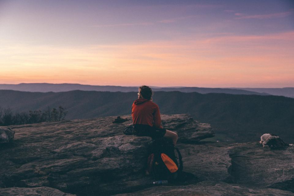 people man male guy travel alone ridge mountain hill peak summit rock sunset dark sky
