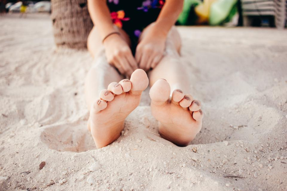 白い砂浜の休暇旅行の足のぼかし