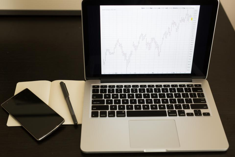 charts graphs data finance macbook laptop computer business working office desk notepad pen smartphone mobile technology objects money