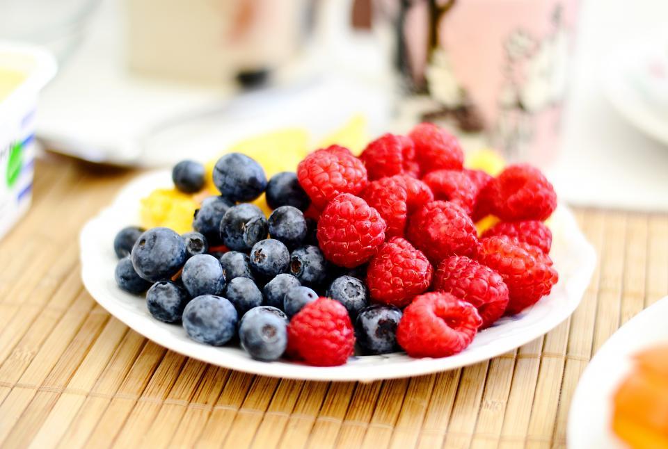 food eat fruits berries raspberries blueberries wood table mat spread plates