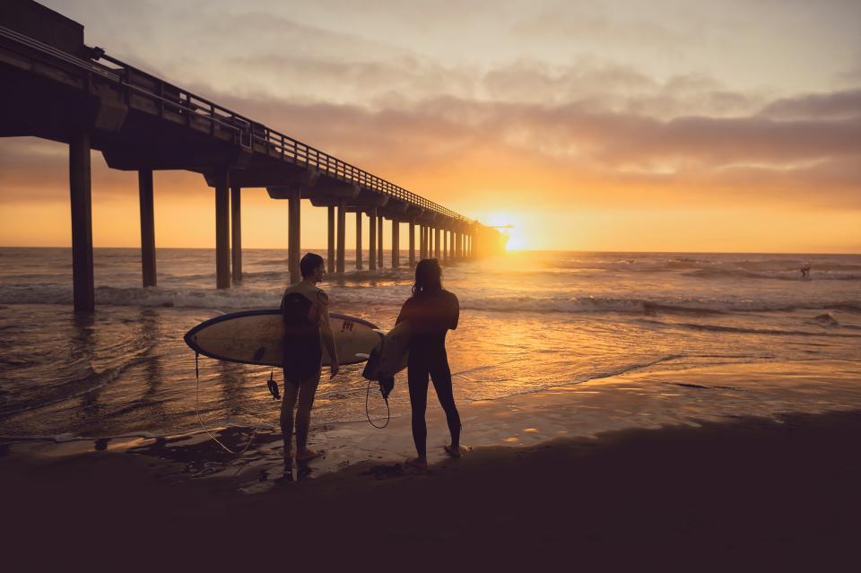 people, man, woman, surfer, surfing, sea, ocean, water, beach, shore, coast, bridge, structure, sky, clouds, sunset, sunrise, sunlight
