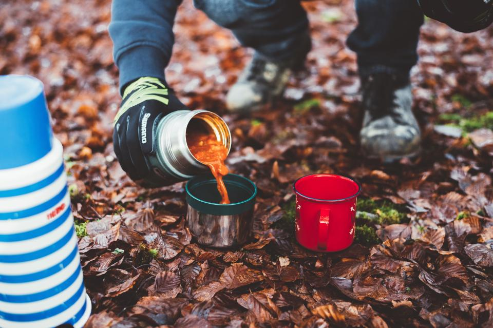 people man food thermos mug hot heat leaves outdoor camping hiking alone adventure trip plants grass