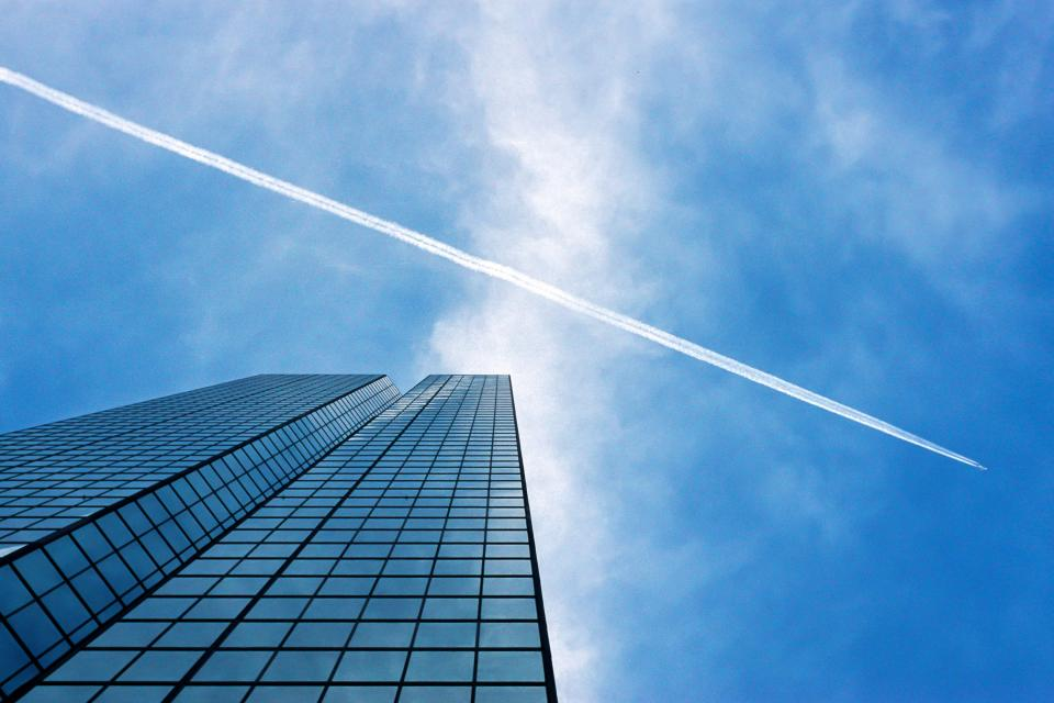 blue sky clouds buildings windows business corporate architecture city urban plane contrail travel transportation