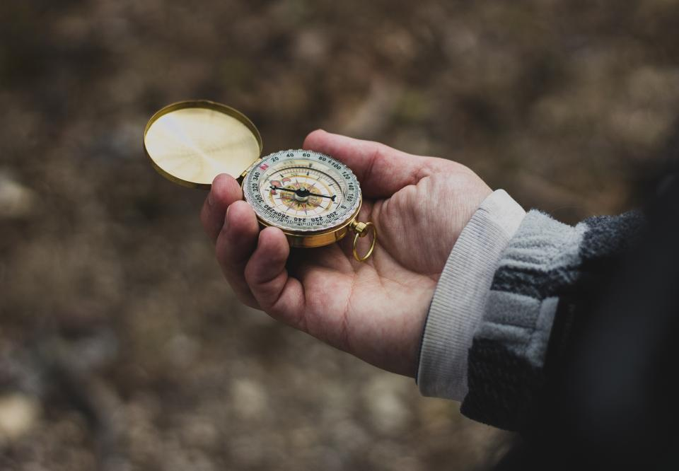 compass metal hand palm travel outdoor blur
