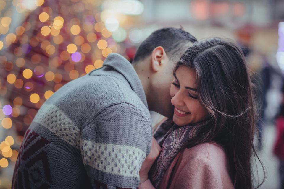 That Girl Cartier - Time and time again girls lose their minds over men who choose someone else. How do you get him to commit? This one's simple. bokeh people couple happy kiss man woman smile christmas lights love heart