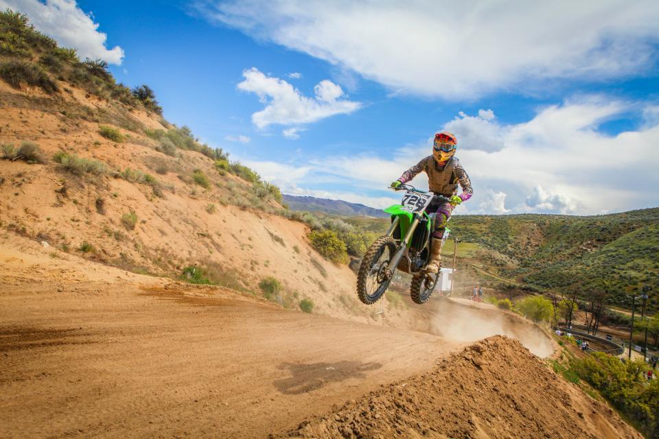 crafts hobby dirt bike motocross jump motorbike soil slope mountains grass sky clouds horizon biker rider