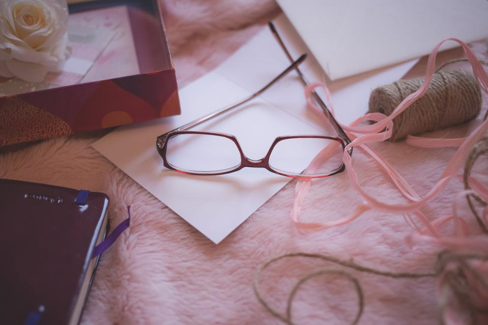 still items things reading glasses yarn box letter journal bokeh
