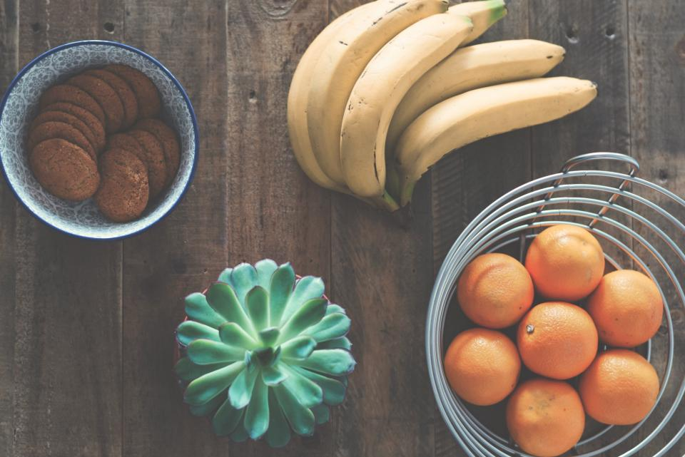 table, food, orange, banana, fruit, health, cookie, pastry, bowl, tray, green, plant, flower, nature