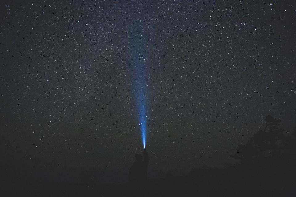 dark night sky stars galaxies atmosphere people alone man flashlight tree