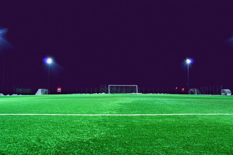 football field, lane, grass, sports, league, spotlights, post, fence, net, signage, goal
