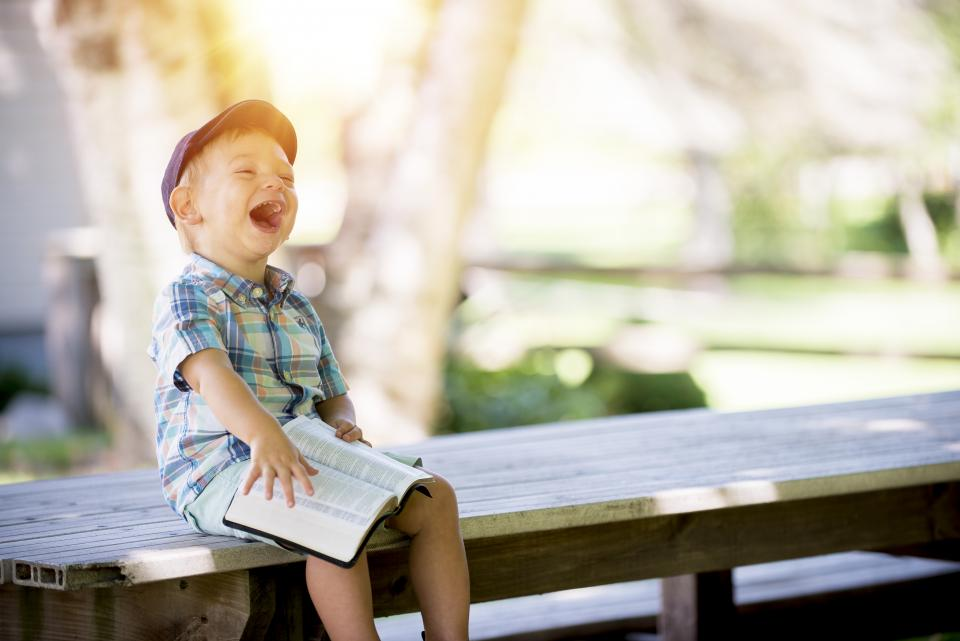 baby kid child people boy laugh happy book bible sitting table outside bokeh