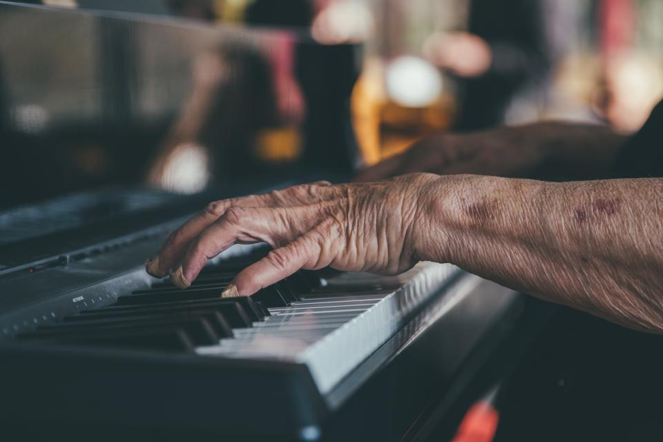 woman old lady people hands play music instrument piano keys still bokeh