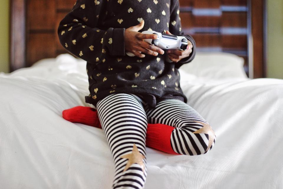 child playing games bedroom joystick star stripe socks bokeh wooden