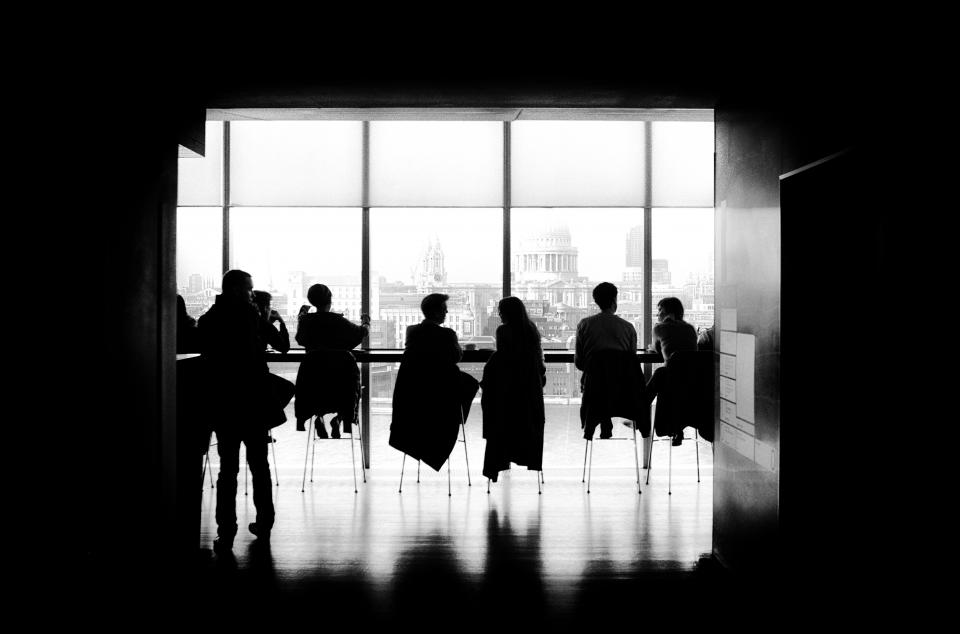 people men girls sitting talking high chairs business black and white building silhouette