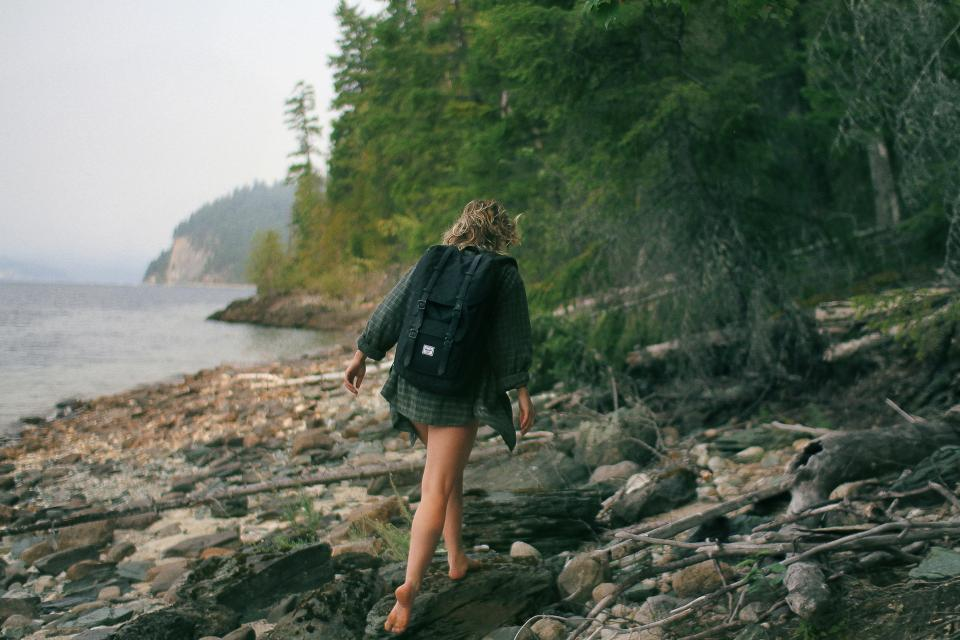 girl hiking trekking walking backpack woman people wood logs coast lake water trees forest woods nature adventure fitness outdoors health