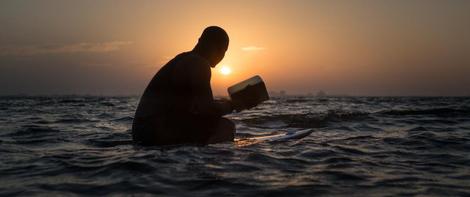 sea ocean water wave nature surfing board lumio book lamp blur dark sunset sky cloud people man